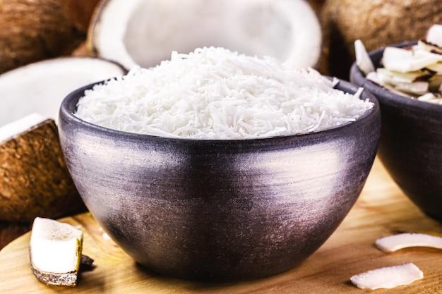 Тертый кокос в глиняной миске на фоне кокоса и кусочков кокоса, кулинарный ингредиент для сладостей