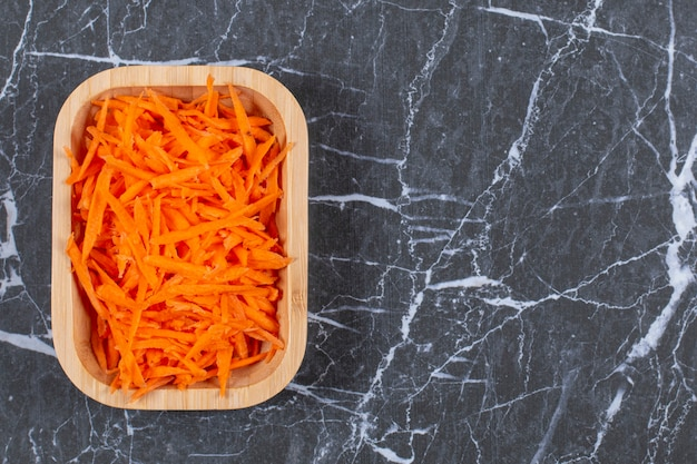 Grated fresh carrot in a brown wooden bowl.