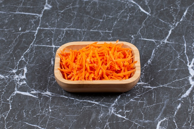 Grated fresh carrot in a brown wooden plate .