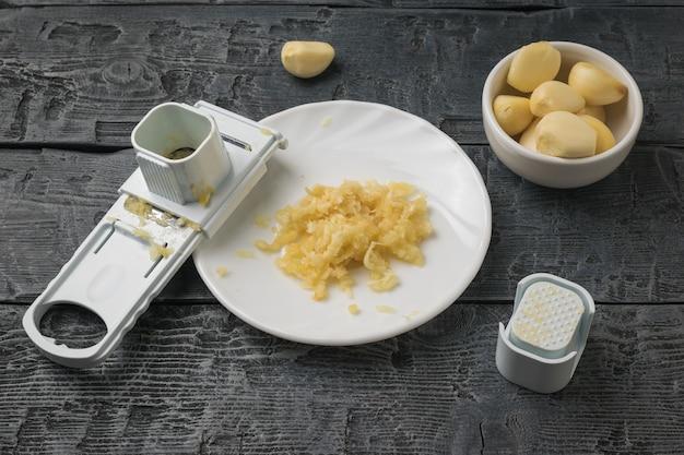 白い皿にニンニクをすりおろし、木製のテーブルにおろし金。キッチンに人気のスパイス。