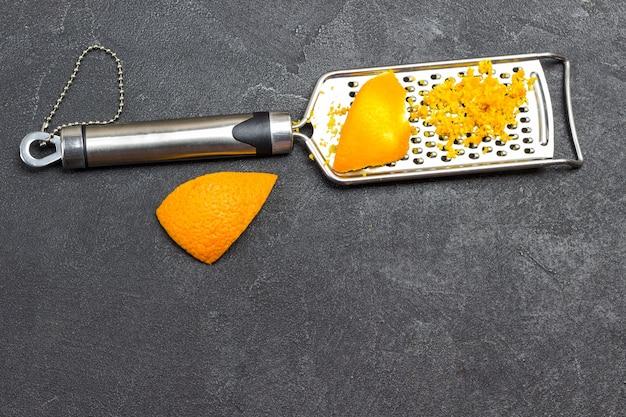 おろし金にオレンジの皮をすりおろした。黒の背景。上面図。コピースペース