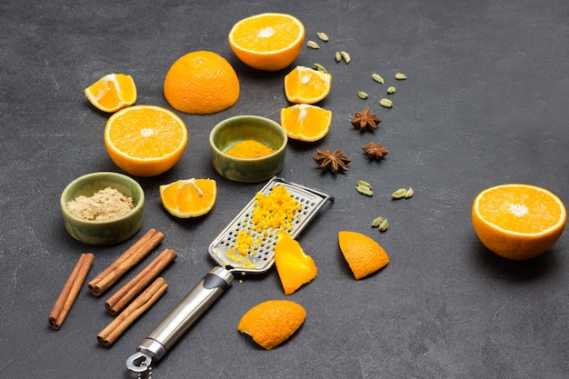 おろし金にオレンジの皮をすりおろした。スライスしたオレンジとドライジンジャー、シナモンスティック、スターアニスをテーブルに。黒の背景。上面図。