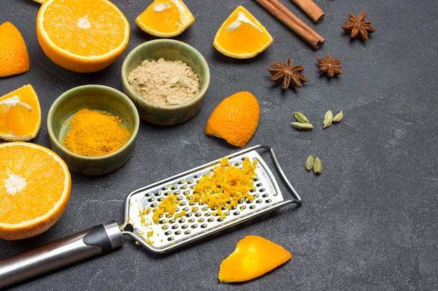 おろし金にオレンジの皮をすりおろした。スライスしたオレンジとスパイスをテーブルに。黒の背景。上面図。