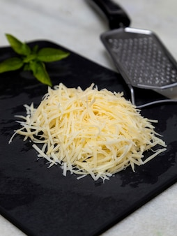 Grated parmesan cheese on black stone with garlic, onion, pepper and other spices