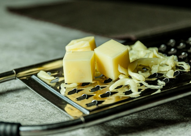 Grated parmesan cheese, cheese grater with cheddar