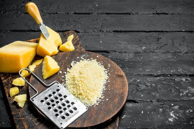 나무 보드에 강판 된 파르 메산 치즈. 검은 소박한 배경.