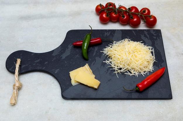 にんにく、玉ねぎ、コショウ、その他のスパイスを加えた黒い石の上にすりおろしたパルメザンチーズ