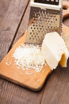 おろし金とテーブルの上にすりおろしたパルメザンチーズ