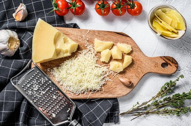 すりおろしたパルミジャーノレッジャーノチーズと木製のまな板に金属のおろし金。灰色の背景。上面図