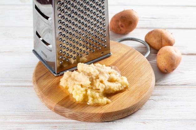 木製のテーブルの上に木製のまな板の上に金属の立っているおろし金とすりおろしたジャガイモ