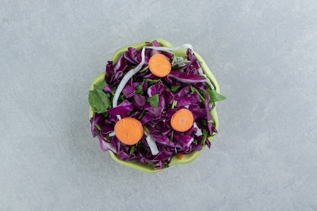 Grated red cabbage, greens and carrots in bowl , on the marble.