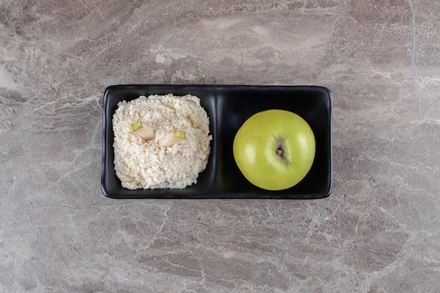 대리석 표면에 그릇에 간 떡과 사과