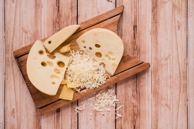 Grated and slices of maasdam cheese on wooden table