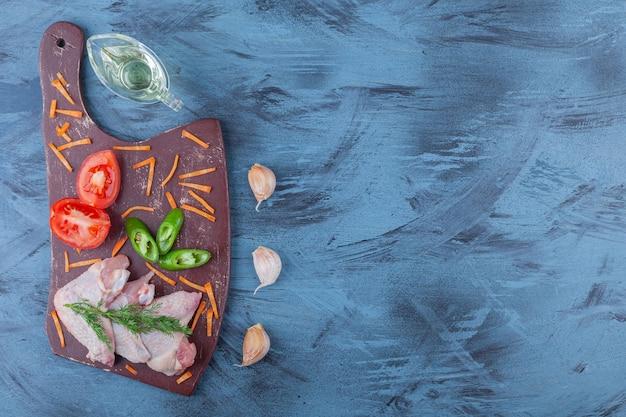 Тертые овощи и куриные крылышки на разделочной доске, на синем фоне.