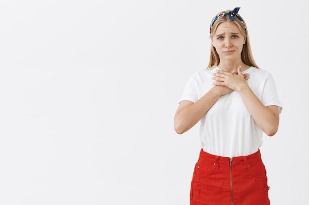 Благодарная и тронутая молодая блондинка позирует у белой стены