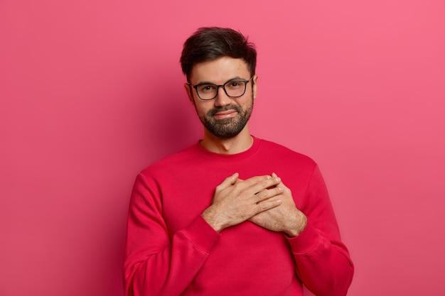 感謝の意を表すひげを生やした男は、手のひらを心に押し付け、心地よい言葉に感動し、触れられ、受け取った贈り物に感謝し、眼鏡とピンクのジャンパーを着て、感謝の気持ちを表し、ピンクの壁にポーズをとる