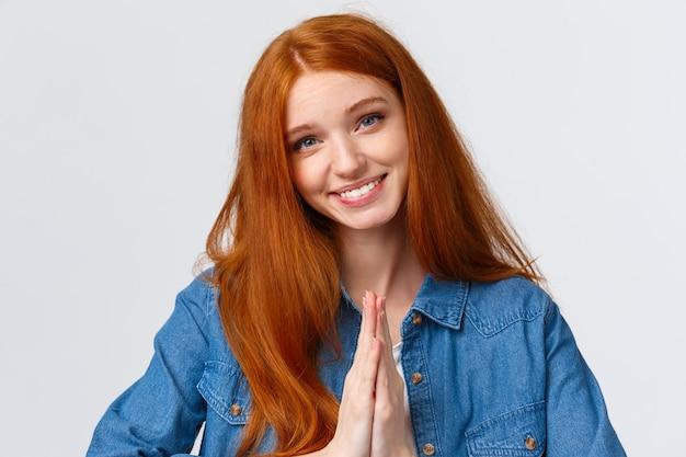 Благодарная очаровательная, милая рыжая женщина ценит помощь, благодарит и вежливо кланяется жестом намасте, держит руки вместе над знаком молитвы на груди, довольная улыбка, белый фон.
