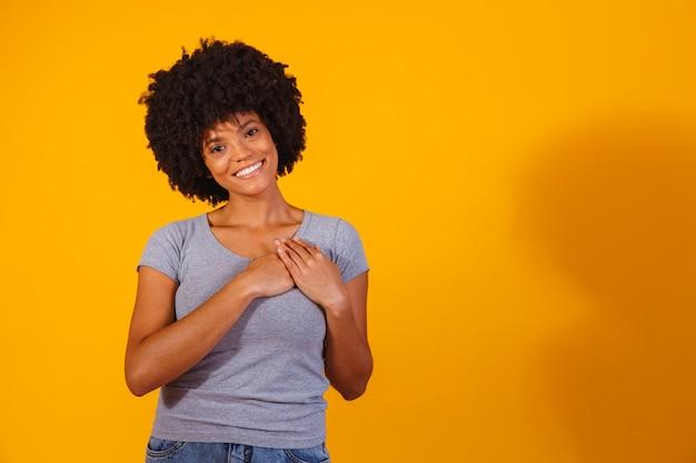 Благодарная обнадеживающая счастливая черная женщина, держащая руки на груди, чувствуя себя довольной благодарной