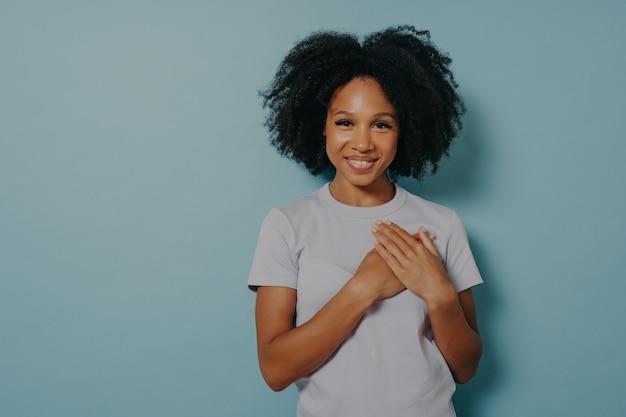 가슴에 손을 얹고 있는 감사하고 희망적인 행복한 흑인 여성, 복사 공간이 있는 파란색 스튜디오 배경에 고립된 마음에서 사랑을 표현하는 만족스럽고 성실한 아프리카 여성. 긍정적인 감정 개념
