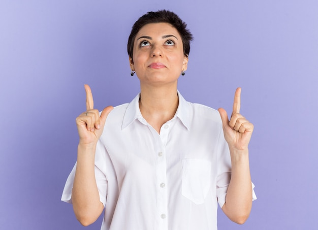 Grateful middle-aged woman looking up doing thank god gesture
