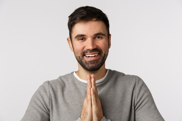 Grateful pleased good-looking bearded man express gratitude and pleasure meet someone, bow politely with hands press together, make pray gesture thanking for help, smiling delighted