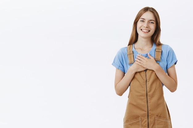 Благодарная красивая молодая девушка, взявшись за руки на груди и радостно улыбаясь