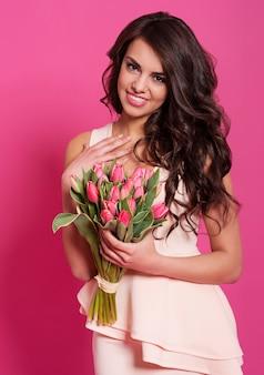 Благодарная улыбающаяся женщина с букетом свежих тюльпанов