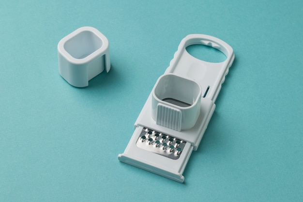 Grater for garlic and chocolate on a blue surface. kitchen appliance.