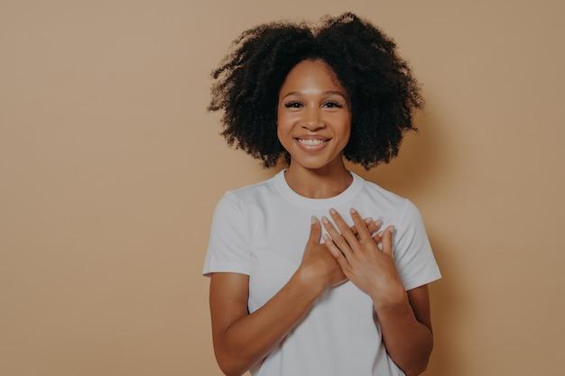 感謝の概念。胸に手をつないで、感謝と愛を示す笑顔の暗い肌の女性を感じて黄色のスタジオの背景に分離された幸せな感謝の若いアフリカの女性