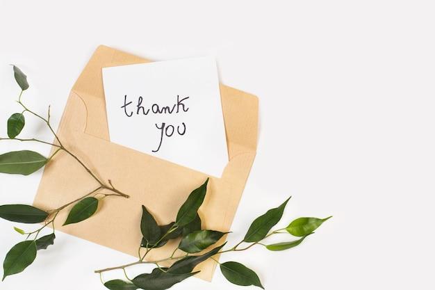白い背景の上の封筒と白い紙の感謝のメモ