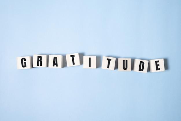 ウッドブロックに書かれた感謝の言葉。あなたのデザイン、コンセプトのための青いテーブルの感謝のテキスト。