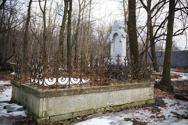 Grave with white monument in snowy cemetery with leafless trees - smolenskoe lutheran cemetery, russia, saint petersburg, march 2021