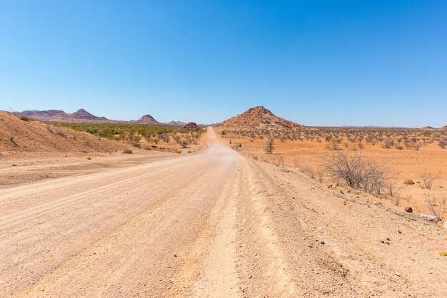 Gravel 4x4 road crossing the colorful desert at twyfelfontein, in the majestic damaraland brandberg, namibia, africa.