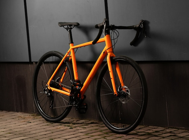 Gravel bicycle. orange bike for offrad cycling on grey wall
