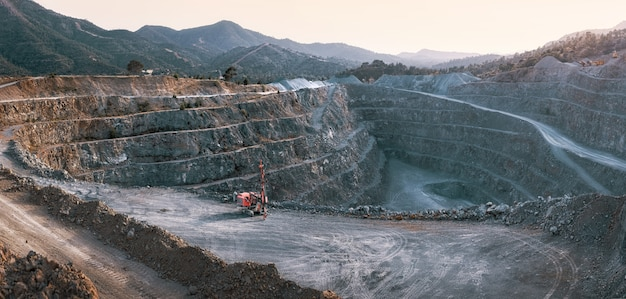 Gravel quarry with terraces piles of stone and red crusher machine with mountains background