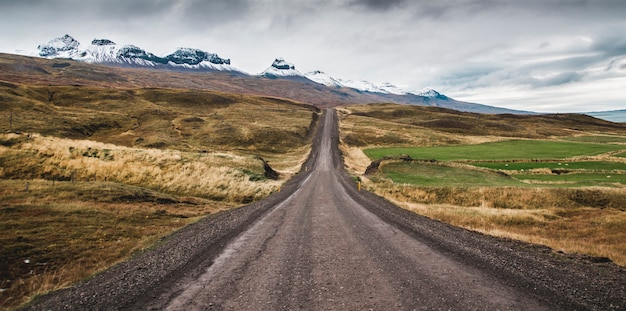 Gravel road in the snowy mountains of iceland after a rainy day with mud