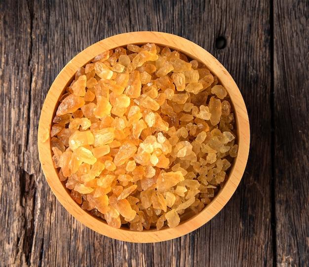 木製テーブルの木製ボウルに砂利砂糖