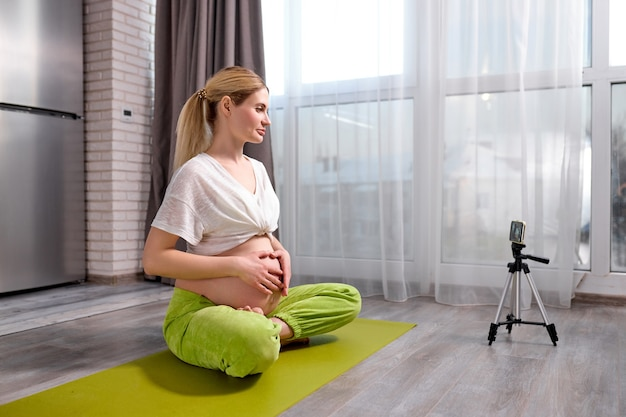 Gravid woman practicing yoga at home with smartphone expectant mother doing prenatal video training class