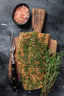 Лосось вяленый gravlax с укропом и солью на деревянной доске. черный фон. вид сверху.