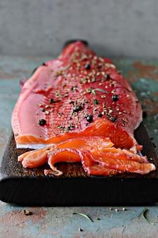 Гравлакс, лосось по-скандинавски вяленый со специями на доске, вид сверху, соленая красная рыба