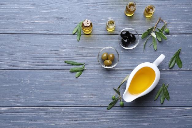 Соусник с оливковым маслом на деревянном столе