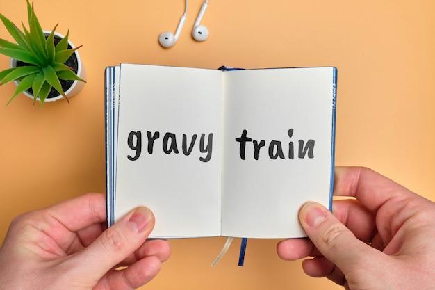 Gravy train - english money idiom hand lettering on wooden blocks