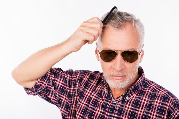 Серый пожилой мужчина в темных очках расчесывает волосы