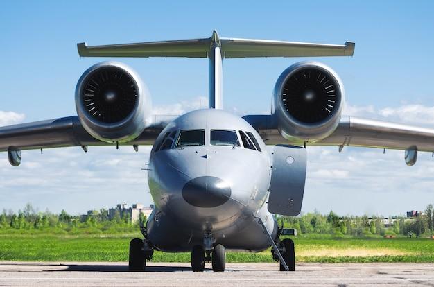 空港の駐車場に駐車されている翼にエンジンを搭載した灰色の飛行機。