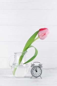 白い木製の机に対してピンクのチューリップと透明なガラスの水差しの近くの灰色の目覚まし時計