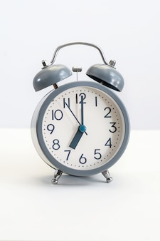 Gray alarm clock on white background, 7 o'clock