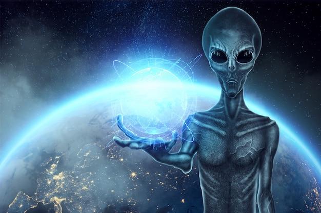 Серый инопланетянин, гуманоид, держит на руке голограмму земного шара. концепция нло, инопланетяне, контакт с внеземной цивилизацией.