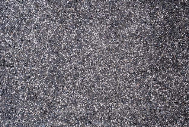 灰色と黒の背景に、道路、フローリング、屋根を舗装するための砂または砂利と暗い瀝青のピッチが混在しています。