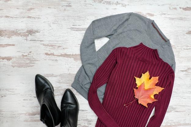 グレーとバーガンディのセーター、黒い靴、カエデの葉。ファッショナブルなコンセプト。