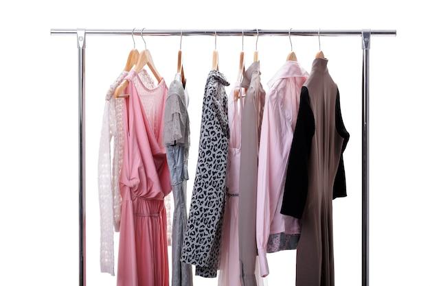 흰색 바탕에 선반에 나무 옷걸이에 회색과 분홍색 여자 옷. 여자의 옷장